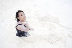使用在沙子海滩的女孩 库存图片