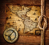 老指南针和绳索在葡萄酒地图 免版税库存照片