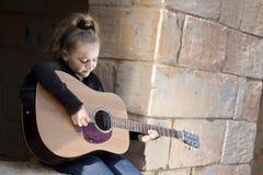 弹吉他的孩子 免版税库存图片