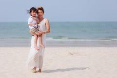 亚裔使用在海滩的妈妈和儿子 库存照片