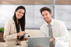 使用微笑的膝上型计算机的愉快的夫妇在家 免版税库存照片