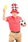 拿着一个黄牌和足球的恼怒的成熟足球迷 免版税库存图片