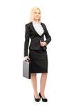 拿着手提箱的一名白肤金发的女实业家的全长画象 免版税图库摄影