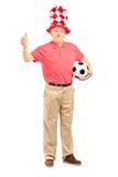 与拿着足球和给星期四的帽子的愉快的成熟爱好者 免版税库存照片