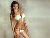 摆在白色游泳衣的性感的妇女照片 图库摄影