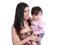 抱着她的女儿婴孩和观看在边的可爱的母亲 库存照片
