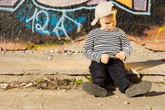 生气的小男孩坐边路 免版税库存照片