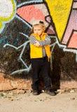 摆在街道画前面的确信的小男孩 库存照片