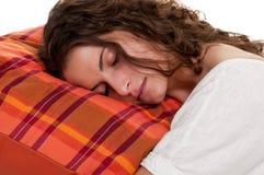 睡觉在一个红色枕头的妇女 免版税图库摄影