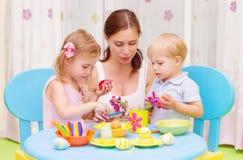 母亲用孩子油漆复活节彩蛋 免版税库存照片