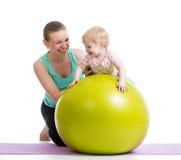 有婴孩做的母亲体操在健身球 免版税库存图片