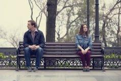 坐在长凳的哀伤的十几岁在公园 免版税库存图片