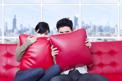 在枕头后的夫妇皮在红色沙发 免版税库存图片