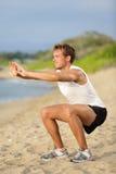健身人训练空气在海滩的蹲坐锻炼 免版税库存照片