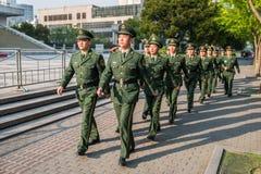 前进在上海池氏街道的朱红色的军队战士  免版税库存照片