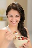 吃碗谷物的可爱的少妇 免版税库存照片