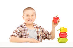 拿着在桌上的一个小微笑的男孩五颜六色的胡椒 免版税图库摄影