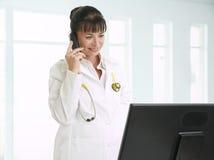女性医生谈话在电话 免版税图库摄影