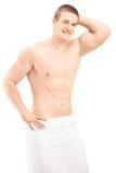 Όμορφος νεαρός άνδρας στην τοποθέτηση πετσετών μετά από το ντους Στοκ Εικόνα