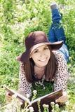 在草的美好的女孩读书 免版税库存照片
