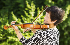 Ανώτερη γυναίκα που εκτελεί τη μουσική υπαίθρια Στοκ Εικόνες