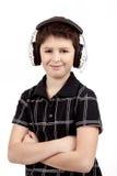 听到在耳机的音乐的一个愉快的微笑的年轻男孩的画象 图库摄影