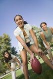 踢橄榄球的三名妇女 库存照片