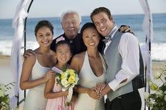 新娘和新郎与家庭在海滩 图库摄影