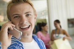Νεαρός άνδρας που καταναλώνει το τηλέφωνο κυττάρων στο πορτρέτο καταστημάτων ιματισμού κοντά Στοκ εικόνα με δικαίωμα ελεύθερης χρήσης
