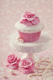与玫瑰色花的杯形蛋糕 库存照片