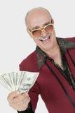 Πορτρέτο του ευτυχούς ανώτερου ατόμου που παρουσιάζει αμερικανικά τραπεζογραμμάτια στο γκρίζο κλίμα Στοκ φωτογραφία με δικαίωμα ελεύθερης χρήσης
