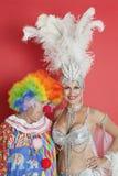 愉快的资深歌舞女郎画象有站立反对红色背景的哀伤的小丑的 免版税库存图片