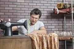 成熟男性在缝纫机的裁缝缝的布料 免版税库存图片