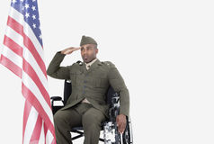 Молодой солдат США в кресло-коляске салютуя американскому флагу над серой предпосылкой Стоковая Фотография RF