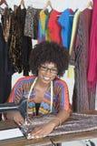 一块非裔美国人的女性裁缝缝的布料的画象在缝纫机的 图库摄影