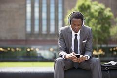 听到与耳机的音乐的非裔美国人的商人画象户外 免版税库存照片