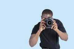 拍照片的非裔美国人的年轻人通过在蓝色背景的数字照相机 免版税库存照片