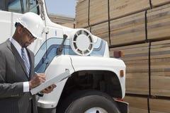 非裔美国人的男性承包商文字笔记,当支持采伐的卡车时 库存图片