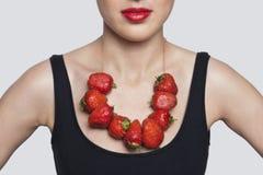 一条妇女佩带的草莓项链的中间部分在灰色背景的 库存图片