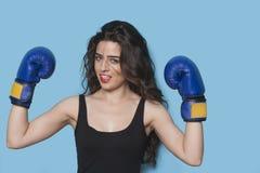 举在胜利的一位美丽的年轻女性拳击手的画象胳膊反对蓝色背景 免版税库存照片