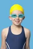 在蓝色背景的愉快的女孩佩带的游泳风镜的画象 免版税库存图片