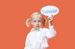 Портрет пузыря чириканья удерживания маленькой девочки против оранжевой предпосылки Стоковое Изображение