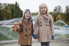愉快的兄弟和姐妹画象握手的军用防水短大衣的在公园 免版税库存图片