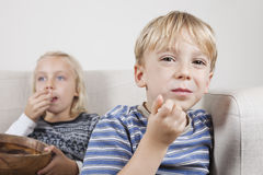 年轻男孩画象有看电视和吃玉米花的姐妹的 库存图片