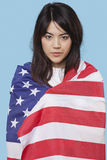 在蓝色背景的美国国旗包裹的爱国的少妇 免版税图库摄影