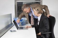 看膝上型计算机屏幕的女实业家和人侧视图书桌在办公室 免版税库存图片