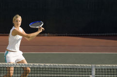 在法院的年轻女性网球员摇摆的球拍 免版税图库摄影