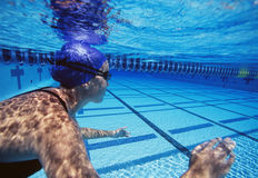 游泳在水池的白种人女性游泳者 免版税库存图片