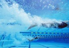 游泳在水池的年轻白种人女性游泳者 免版税图库摄影