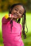 一个逗人喜爱的年轻黑人女孩的室外画象-非洲人民 库存照片